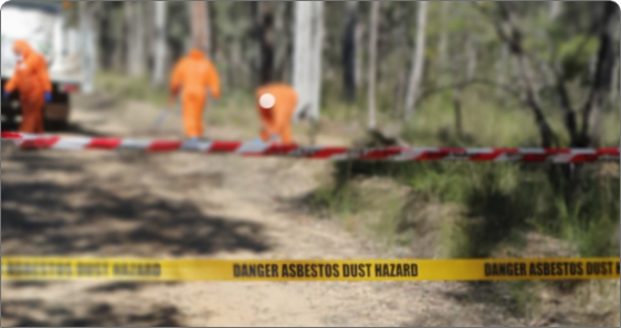 Danger asbestos dust hazard strip with construction workers wearing construction suits behind the marked area